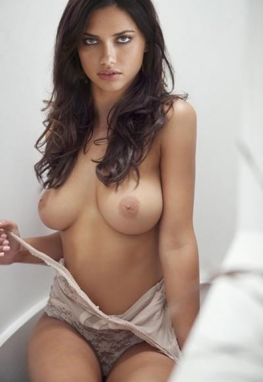 naked girl standing on a bed